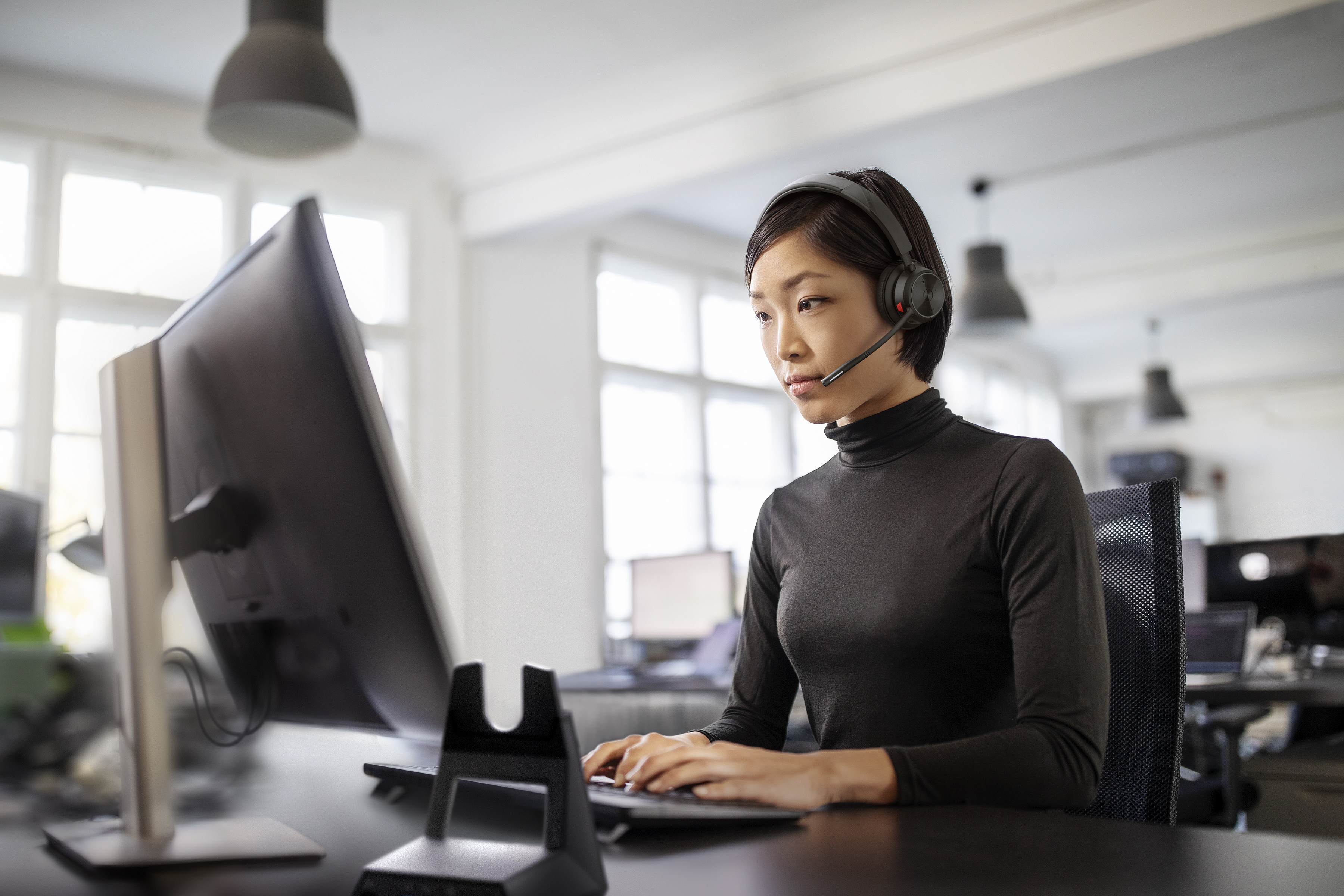 Woman working at her desk in open plan office with Savi 7300 Office Series